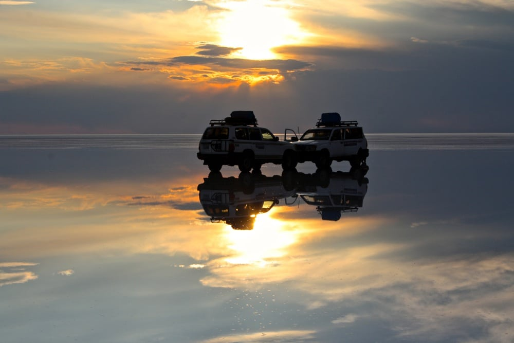 sunset on wet salar de uyuni on one of the best road trips in the world