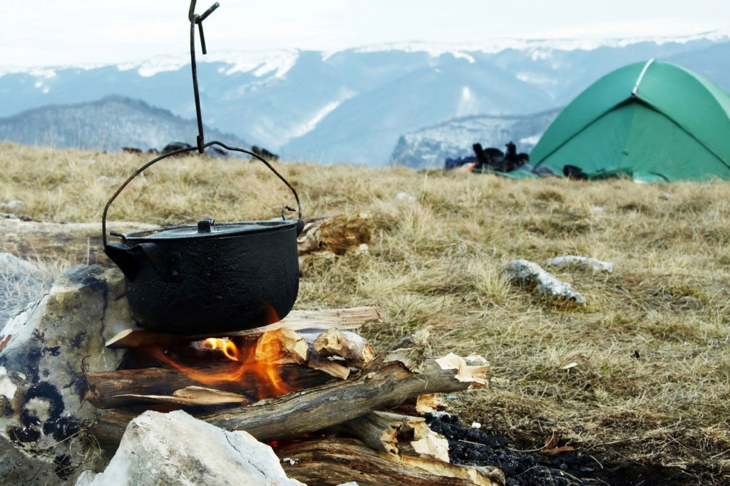 A campfire positioned away from a tent