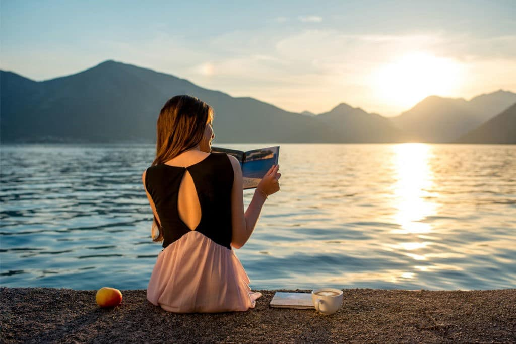 how to improve your vocabulary: woman reading by the water