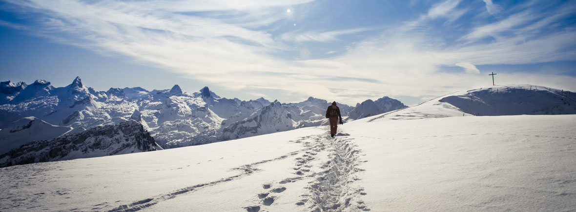 Man walks across a winter hiking landscape