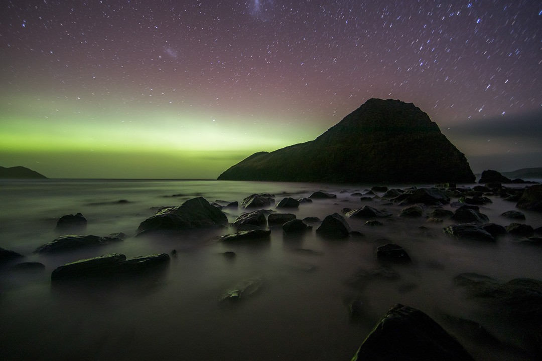 The southern lights illuminate Lion Rock in south Tasmania