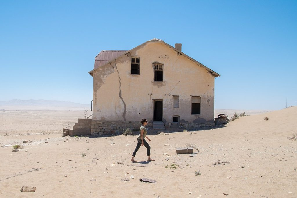 Kia walks past a crumbling building in the ghost town of Kolmanskop