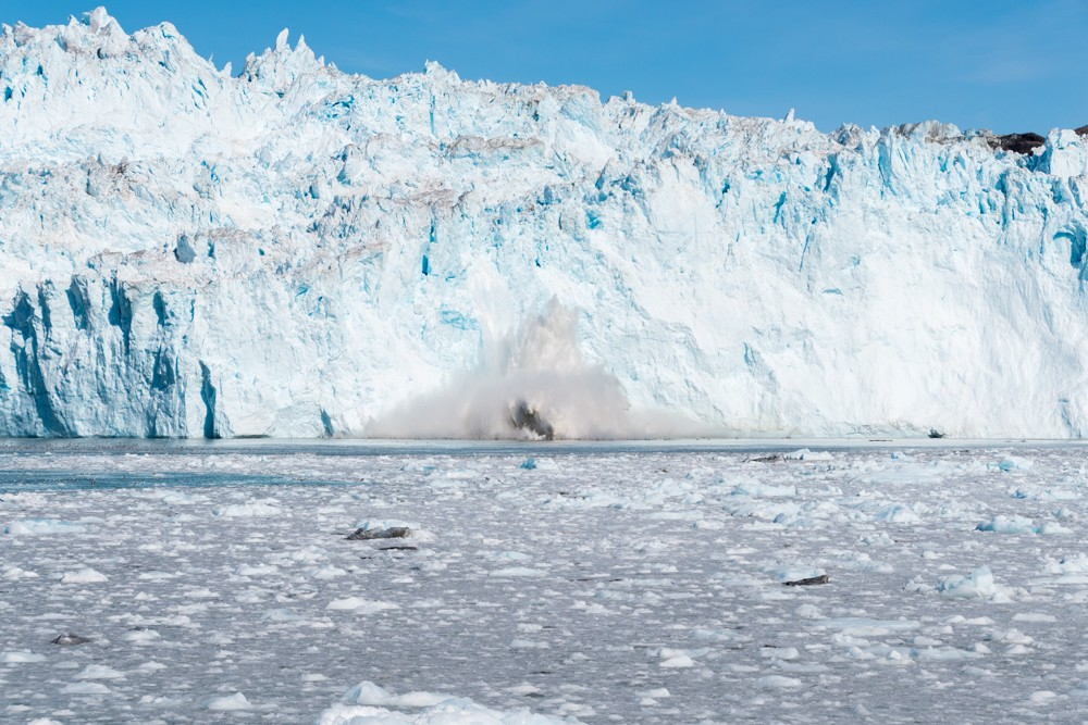 A chunk of ice carves off Eqi Glacier