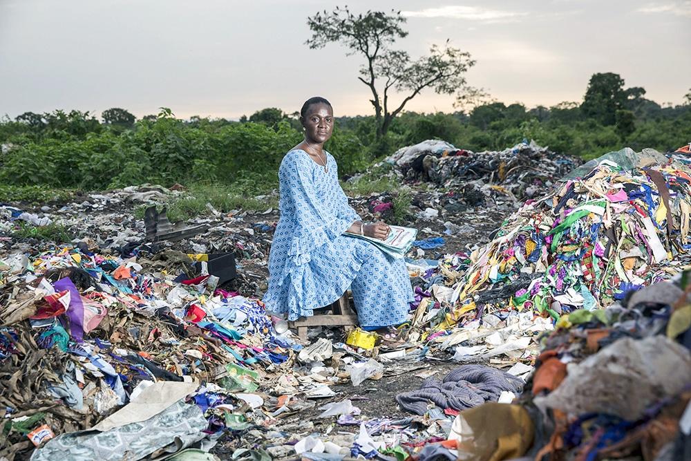 Isatou Ceesay est assise au milieu d'un tas de déchets plastiques
