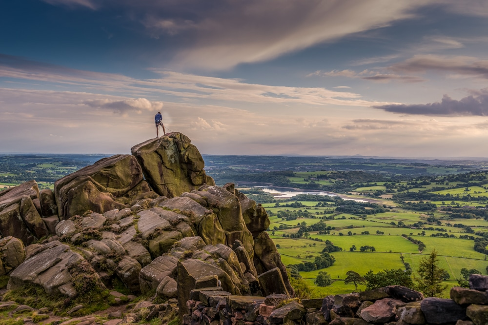 A climber enjoys the view from the Roaches