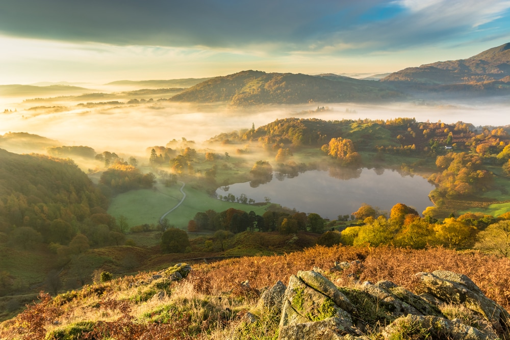 Morning fog lingers over Loughrigg Tarn in the Lake District