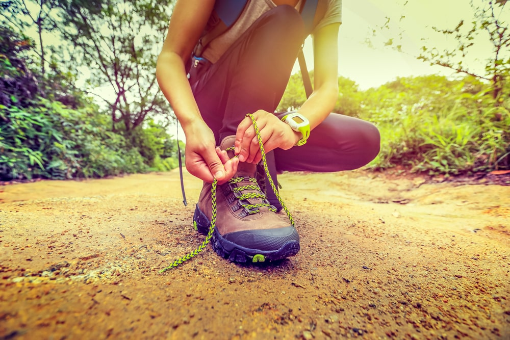 A woman ties her hiking boots