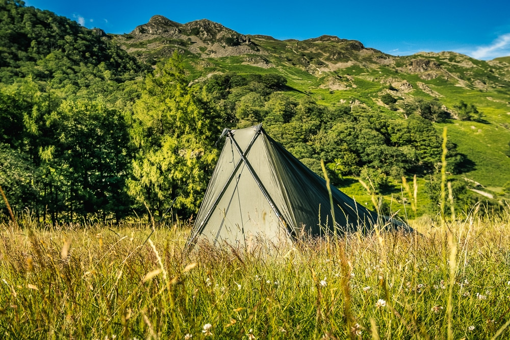 Tent pitched using trekking poles with hills behind
