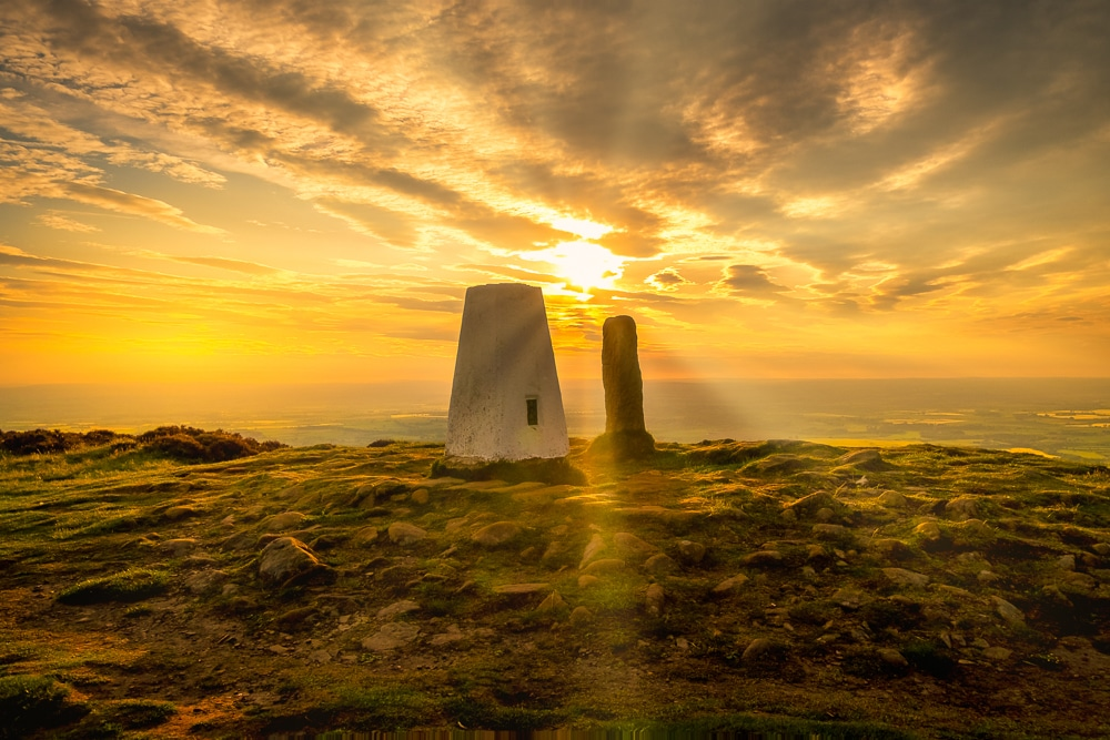 The trig point on Carlton bank with the sun setting behind