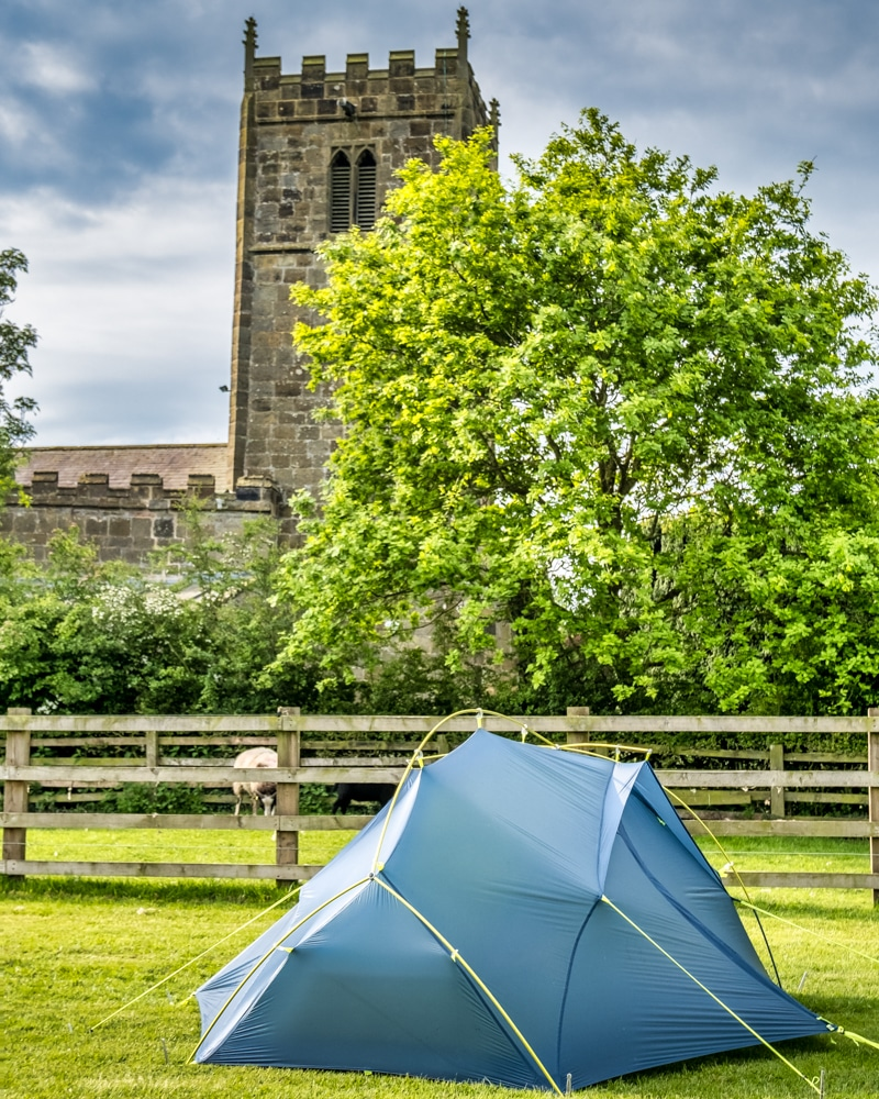 Peter's tent pitched in front of a church in Danby Wiske on the Coast to Coast Walk